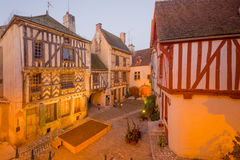 Square with half-timbered houses, in the medieval village Noyers. Sunrise view of a square place de la petite etape aux vins, with half-timbered houses, in the Royalty Free Stock Photos