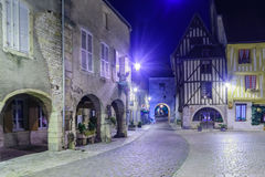 Square with half-timbered houses, in the medieval village Noyers. NOYERS-SUR-SEREIN, FRANCE - OCTOBER 11, 2016: Night view of the main square place de hotel de Stock Photos