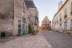 Square with half-timbered houses, in the medieval village Noyers. NOYERS-SUR-SEREIN, FRANCE - OCTOBER 12, 2016: Sunrise view of a square place du grenier a sel Royalty Free Stock Images