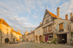 Square with half-timbered houses, in the medieval village Noyers. NOYERS-SUR-SEREIN, FRANCE - OCTOBER 11, 2016: Sunset view of the main square place de hotel de Stock Photo