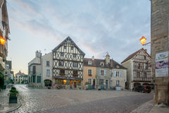 Square with half-timbered houses, in the medieval village Noyers. NOYERS-SUR-SEREIN, FRANCE - OCTOBER 11, 2016: Sunset view of the main square place de hotel de Stock Photos