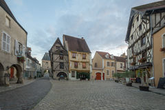 Square with half-timbered houses, in the medieval village Noyers. NOYERS-SUR-SEREIN, FRANCE - OCTOBER 11, 2016: Sunset view of the main square place de hotel de Stock Photography