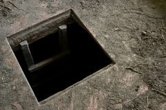 Hole in floor of old house leading to cellar. A square hole in the dirty floor of an abandoned wooden house leading deep into dark cellar. Horror, terror stock images
