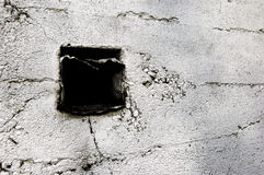Square hole in wall. A square hole with scrap metal on a white painted cement wall Stock Photography