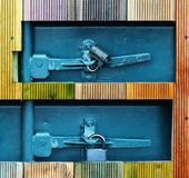 Holes in a wooden wall with two padlocks on a grey metallic door. Square holes in a wooden wall with two small padlocks on a grey metallic door. Close up Royalty Free Stock Photography