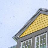 Square Home with yellow wall and glass windows against cloudy sky in Daybreak Utah. The roof is covered with a sheet of fresh snow during winter season royalty free stock photo