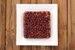 Square homemade yummy chocolate cake with cherries in white squa. Re plate on wooden table above Stock Images