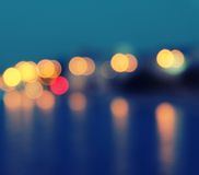 Square image of a blurred city lights with bokeh effect reflected on water. Stock Photography