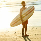 Square image of surfer holding a surfboard under his arm. Square image of male surfer standing on the beach while holding a surfboard under his arms, looking off Stock Photo