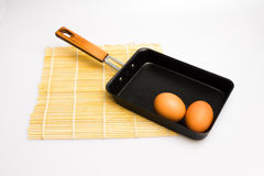 Square japanese frying pan with eggs and sushi mat. Square japanese frying pan with eggs on sushi mat Royalty Free Stock Photos