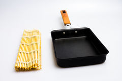 Square japanese frying pan and sushi mat Royalty Free Stock Photography