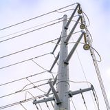 Square Looking up at a towering metal post supporting overhead power lines stock image