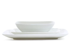 Square Meal. Set of white square dinner plates on white Stock Photos