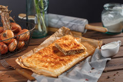 A square meat pie. Delicious meat pie on a wooden surface. A square piece of meat pie on a rectangular meat pie on a wooden surface against the background of the royalty free stock photos