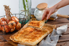 A square meat pie. A female hand holds a piece of a square pie on a wooden kitchen spatula. A square piece of meat pie on a rectangular meat pie on a wooden stock photo