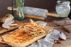 A square meat pie. A square piece of meat pie on a rectangular meat pie on a wooden surface against the background of the ingredients from which it was made royalty free stock image