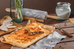 A square meat pie. A square piece of meat pie on a rectangular meat pie on a wooden surface against the background of the ingredients from which it was made stock photos