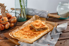 A square meat pie. A square piece of meat pie on a rectangular meat pie on a wooden surface against the background of the ingredients from which it was made royalty free stock photography