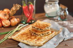 A square meat pie. Potato Square Pie with Red Pepper and Onion Stems A square piece of meat pie on a rectangular meat pie on a wooden surface against the Royalty Free Stock Photography