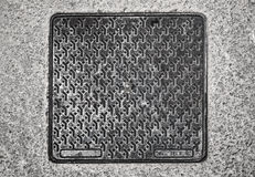 Square metal hatch on asphalt Royalty Free Stock Photo