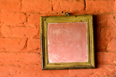 Square mirror on a brick wall Stock Photo