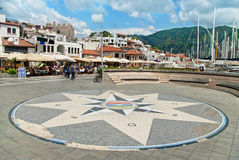 Square with mosaic compass near restaurant street and marina Royalty Free Stock Photography