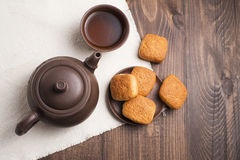 Square mug of tea with shortbread biscuits. On a brown table and a napkin Stock Image
