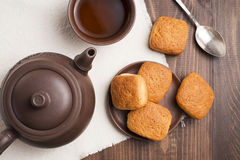 Square mug of tea with shortbread biscuits. On a brown table and a napkin Royalty Free Stock Images
