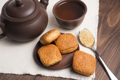 Square mug of tea with shortbread biscuits. On a brown table and a napkin Stock Images