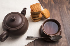 Square mug of tea with shortbread biscuits. On a brown table and a napkin Stock Photos