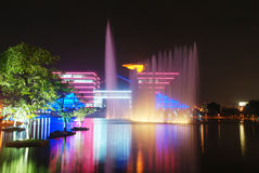 Square night scene. Under light Paris green tree, artificial lake water under colored lantern a riot of color, passes through eruptive fountain which raises high Stock Photos