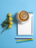 Square notepad on springs with white kraft paper, pencil, yellow rose and cup of tea are on blue background. Copyspace Royalty Free Stock Photos