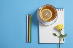 Square notepad on springs with white kraft paper, pencil, yellow rose and cup of tea are on a blue background. Stock Image
