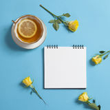 Square notepad on springs with white kraft paper, yellow rose and cup of tea are on a blue background. Stock Photo