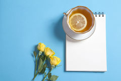 Square notepad on springs with white kraft paper, yellow rose and cup of tea are on a blue background. Stock Photography