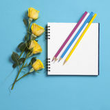 Square notepad on springs with white kraft paper with a yellow rose lay on a blue background. Copyspace Stock Photos