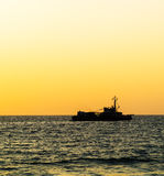 Square orange vivid ocean horizon with ship silhouette Stock Images