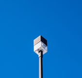 Square outdoor light on post on blue sky. Royalty Free Stock Image