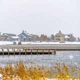 Square Panorama of a lake in Daybreak Utah with wooden decks and snowy shore in winter. Distant homes and buildings can be also be seen against the cloudy sky stock photo