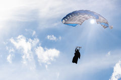 Square parachute canopy in blue sky. In sun rays, inflated, with skydiver silhouette in wingsuit. Low-altitude jump with basejumping gear. Copy-space on sky Royalty Free Stock Photos