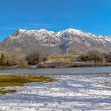 Square Park with a scenic view of a lake and snow capped mountain under vivid blue sky royalty free stock photography