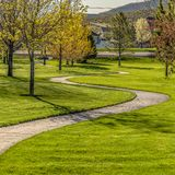 Square Pathway winding through a terrain with rich green grasses and young trees. The path leads to the road with view of mountain and sky in the distance royalty free stock photos
