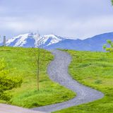 Square Paved pathways on a hill covered with vibrant green grasses. The snow covered peak of a mountain against cloudy sky can be seen in the distance royalty free stock photo