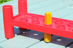 A square peg in a round hole. Two rows of empty round holes. One square peg is in one of the round holes Stock Photos