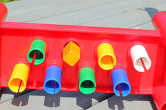 A square peg in a round hole. Two rows of round pegs in round holes and an odd square peg in a round hole Royalty Free Stock Photography