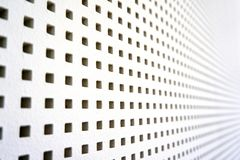 Square perforated sound barrier. Wood wall white acustic grate metal texture wallpaper steel surface iron abstract background hole structure metallic grid stock image