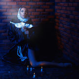 Square photo of nun near brick wall with candles. Square photo of nun sitting near brick walls with candles on floor Royalty Free Stock Photos