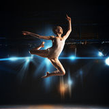 Square photo of young blonde ballet dancer in jump on stage Royalty Free Stock Photography