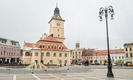 The square Piata Sfatului and the center building Casa Sfatului in winter time, cloudy day and snowing. Stock Images
