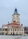 The square Piata Sfatului and the center building Casa Sfatului in winter time, cloudy day and snowing. Stock Photos